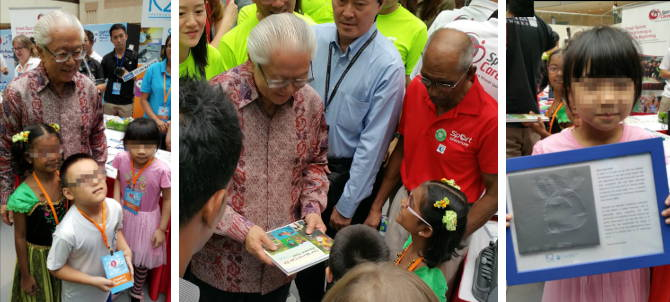 """Our thanks to our President, Dr Tony Tan, for gracing the occasion and making the day extra special for our three students, """"Amy"""", """"Ben"""" and """"Carol"""". The President posed for pictures and was presented with the very first independent tactile drawing ever made by our blind student, """"Amy"""", and a copy of our coffee table book, """"Our World Can Be Vibrant Too!"""", containing testimonials and words of encouragement from eye care professionals, school teachers, students, parents, volunteers and staff."""