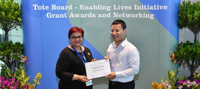 SG Enable Award - iC2 Executive Director Jamuna receiving a grant award from Tote Board